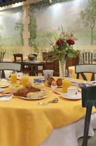 Détail du jardin d'hiver, salle de restaurant du château hôtel de La Rozelle avec une table dressée